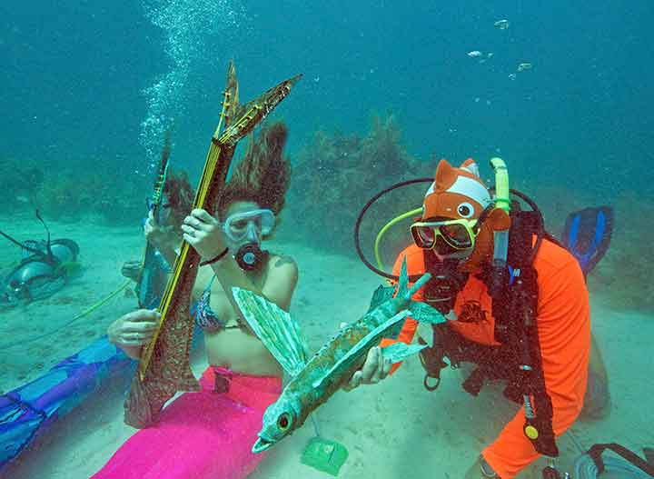 Nicole Pacha, Sarah Brunner and Larry Threlkeld, pretended to play underwater instruments sculpted by a local artist at the U/W Music Fest.