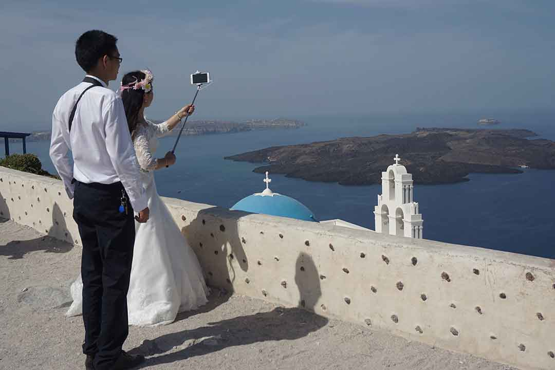 A bridal oouple taking photos with a selfie stick was an unusual sight. Santorini is a popular wedding destination. (Photo: Debbra Dunning Brouillette)