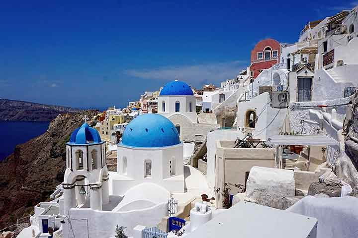 The iconic blue-domed church dominates the foreground in the oft photographed village of Oia.